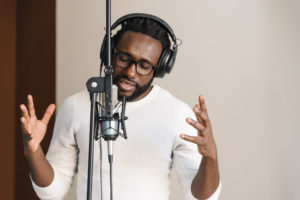 | African young man singing on musical studio.