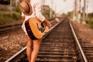| Girl walking on railway wish guitar